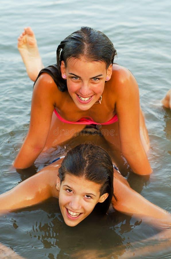 Två tonårs- flickor som har gyckel i floden arkivfoto