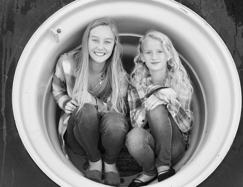 Två tonårs- flickor som huka sig ned i traktorgummihjul royaltyfri bild