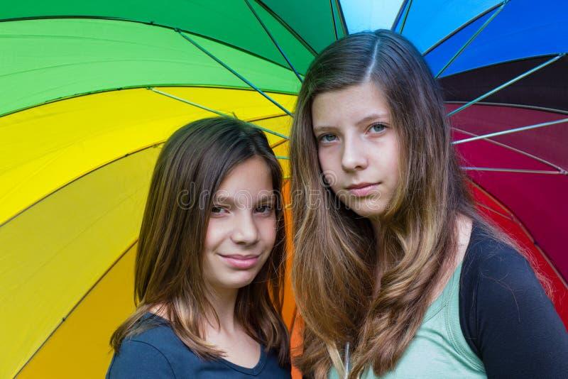 Två tonårs- flickor under regnbågeparaplyet royaltyfri foto