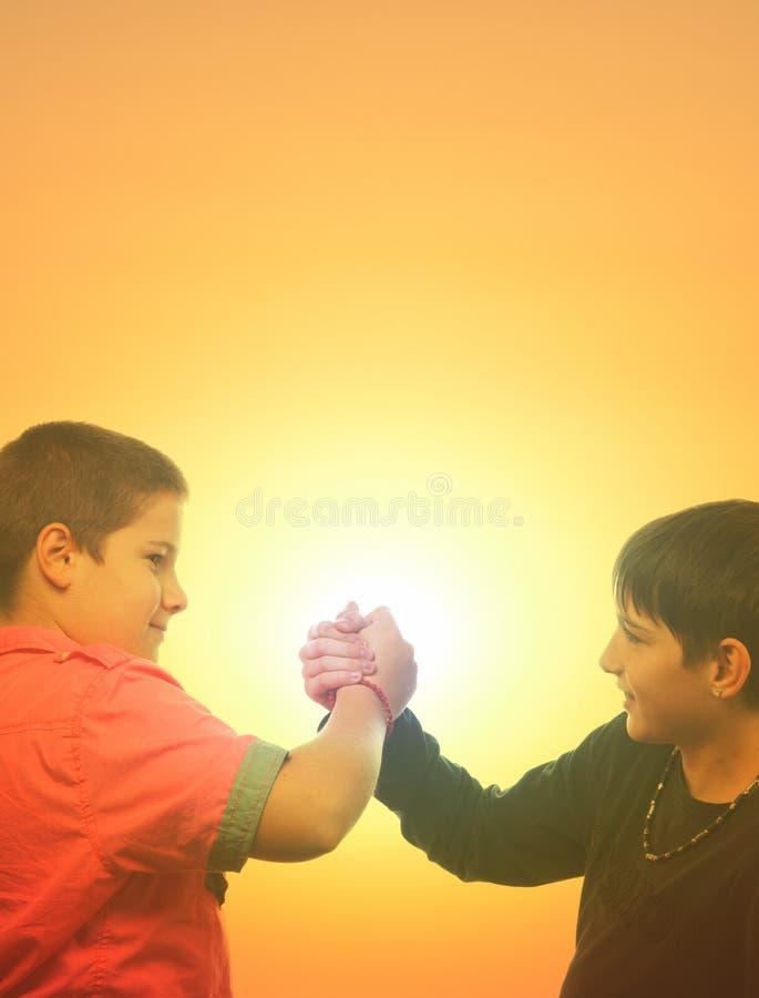 Två tonårs- pojkar som skakar händer i sommar royaltyfria bilder