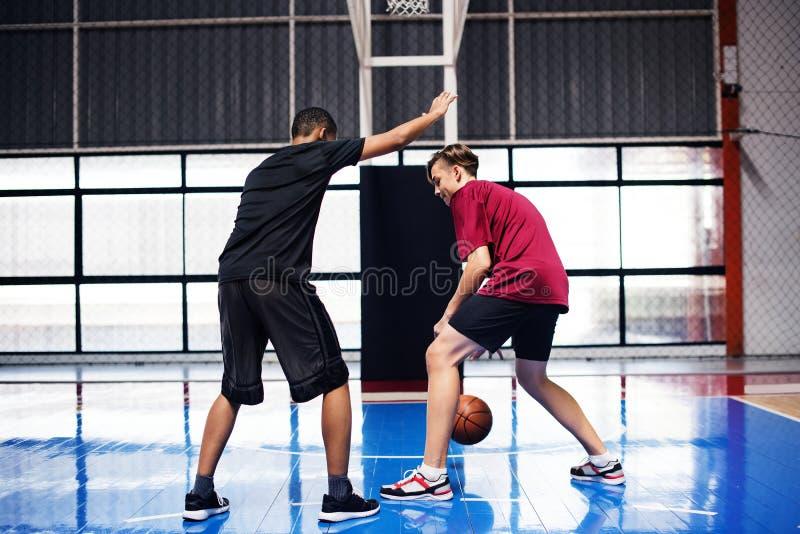 Två tonårs- pojkar som spelar basket tillsammans på domstolen arkivfoton