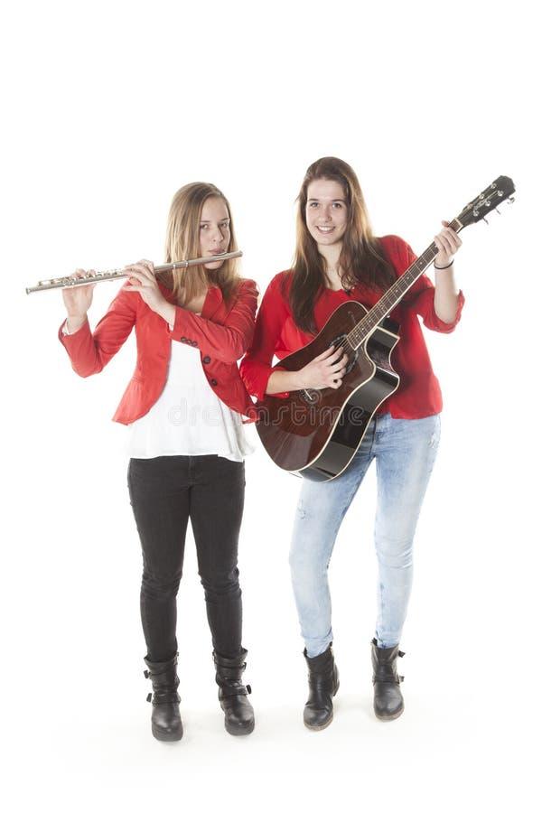 Två tonårs- systrar spelar flöjten och gitarren i studio arkivfoton