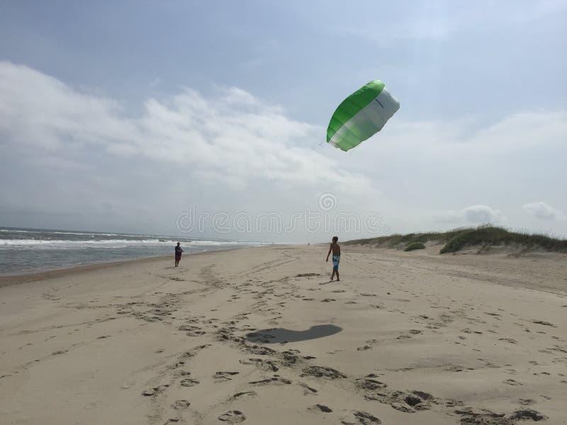 Två tonårspojkar som flyger en grön kit på stranden royaltyfria bilder