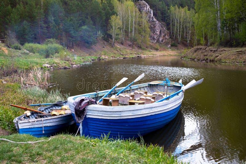 Två träfartyg med åror på banken av skogfloden, skog fotografering för bildbyråer