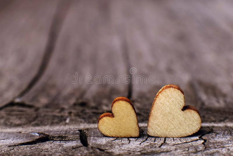 Två trähjärtor som utmärkt förläggas på en tappningträbakgrund Kopiera utrymme, förälskelsebegrepp arkivfoton