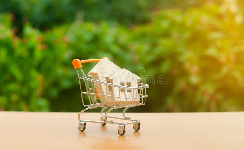 Två trähus i en handla vagn på naturbakgrund Attraktivt investera stigande priser tillgång och efterfrågan hastigheter av försälj royaltyfria foton