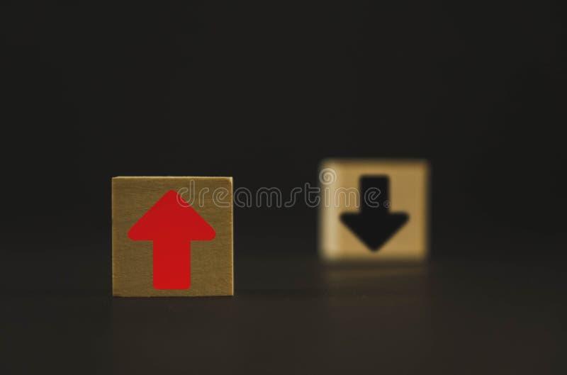 Två träkuber på tabellen är rött och svart rött hjälpmedel tillväxt och utveckling, och den svarta pilen betyder nedgången och de royaltyfri bild