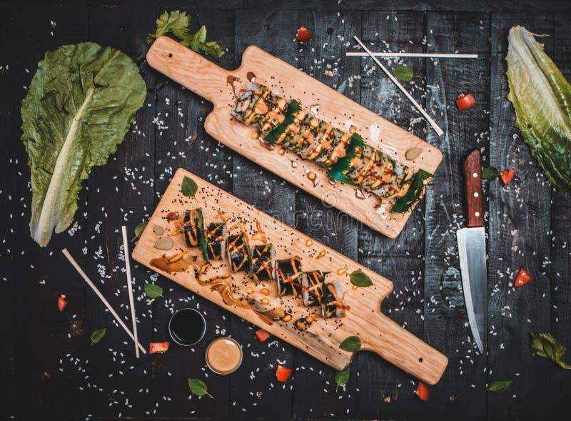 Två träplattor med sushi förlade på en tabell med kniven och grönsallat royaltyfri bild