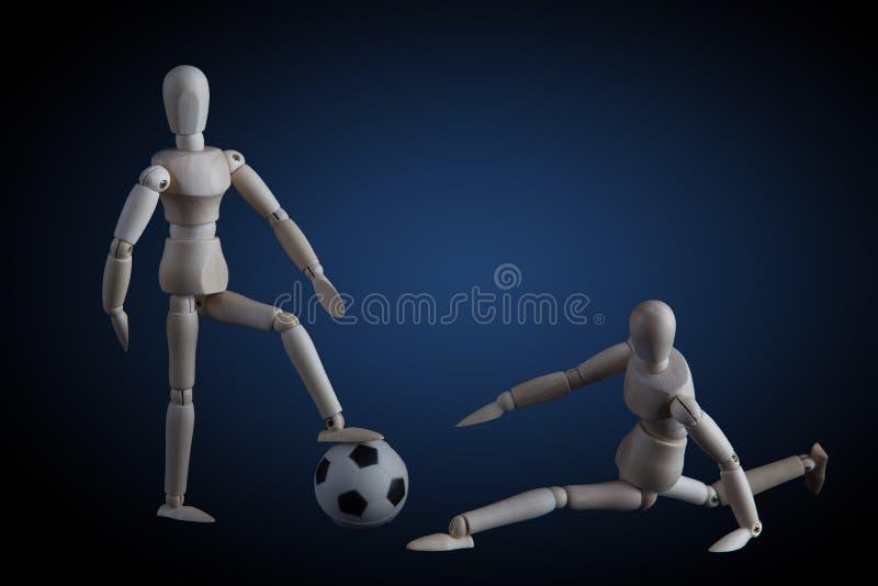 Två trästatyetter som spelar fotbollbegrepp på mörk bakgrund w arkivbilder