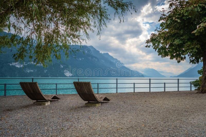 Två trästolar på promenaden av Brienz, Schweiz arkivfoto