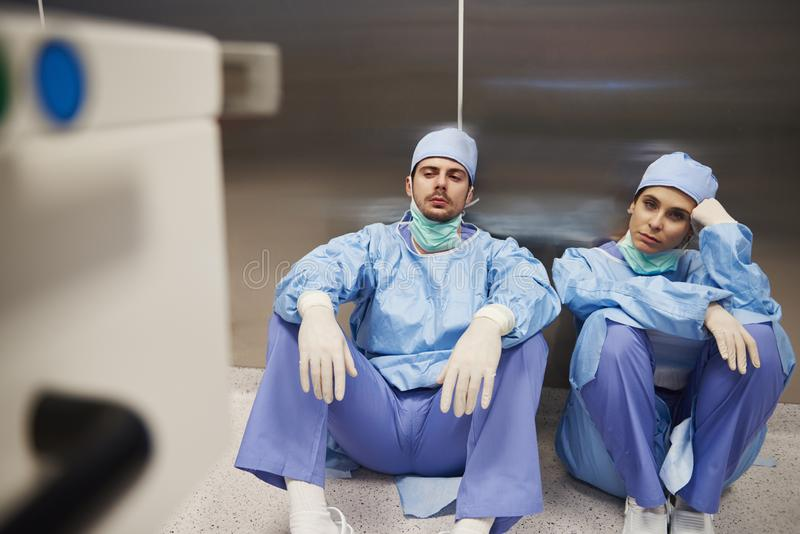Två trötta kirurger efter operationen i korridoren arkivbild