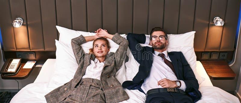 Två tröttade affärsfolk som lägger på säng i ett hotellrum royaltyfria foton