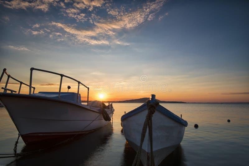 Två traditionella träfiskebåtar i havet Fiskebåtar som binds upp i hamn i slutet av dagen Solnedgång nära Blacket Sea royaltyfri fotografi
