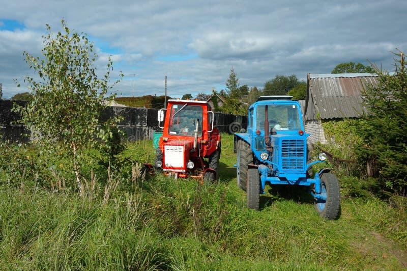 Två traktorer i en by nära den wood röd och blå tracen för hus, royaltyfri fotografi