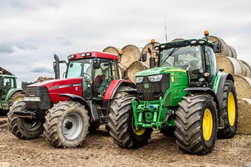 Två traktortraktorer som parkeras upp med höbaler royaltyfri bild