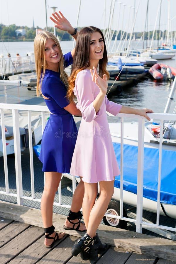 Två trendiga flickor som vilar på en marina royaltyfri foto