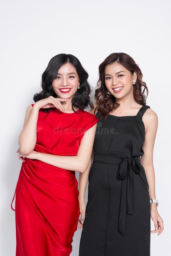 Två trendiga kvinnor i trevliga klänningar som tillsammans står, och havi royaltyfria foton