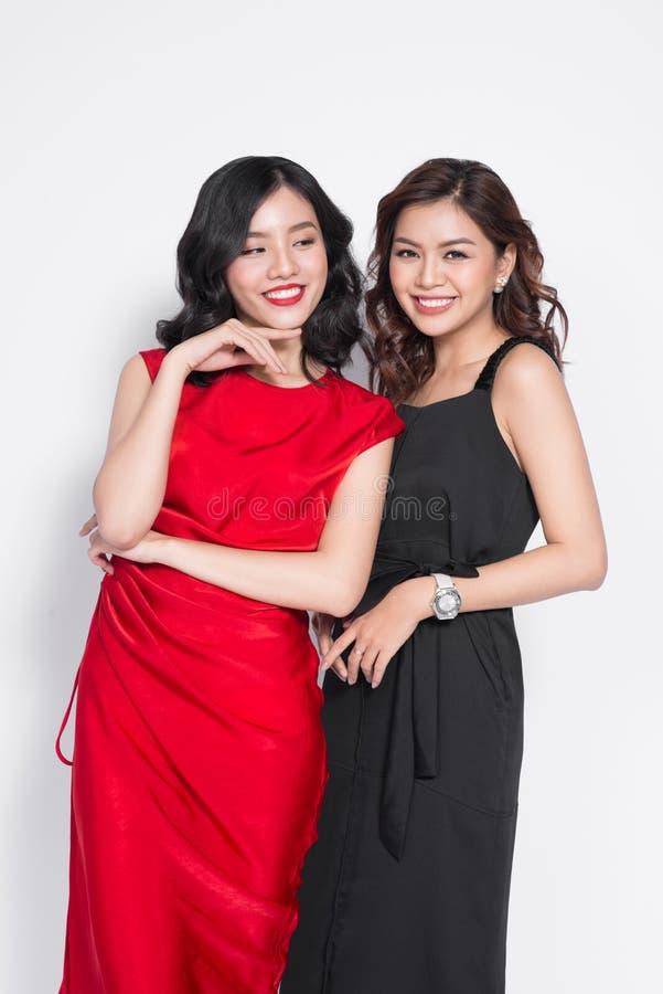 Två trendiga kvinnor i trevliga klänningar som tillsammans står, och havi royaltyfri fotografi