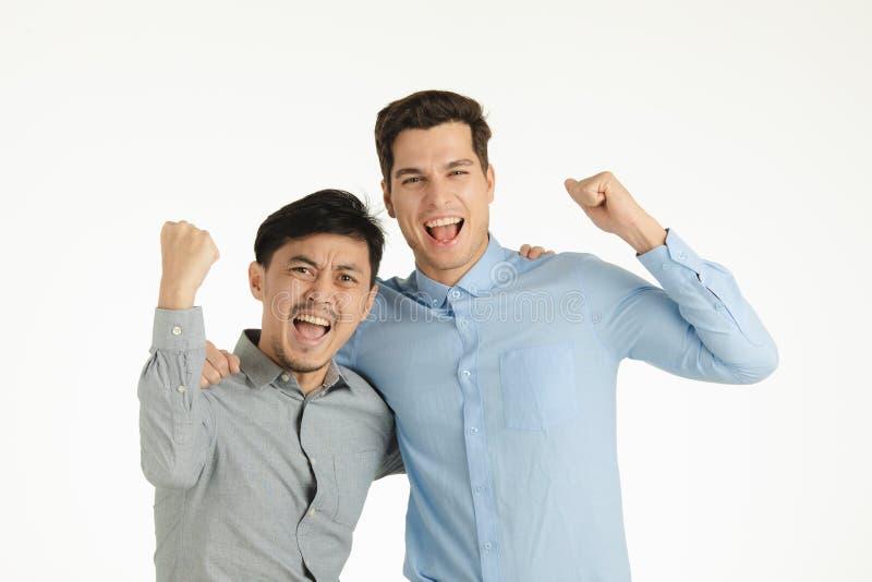 Två triumferande män poserar fotografering för bildbyråer
