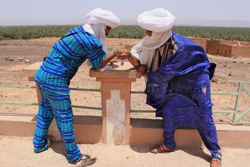 Två Tuaregs i blått klär och vita turbaner som spelar leken arkivbilder