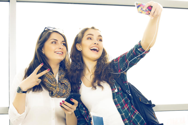 Två turister för unga kvinnor som rymmer ett pass och, gör selfieterminalen arkivbilder