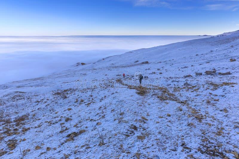 Två turister går ner bergvägen till molnen fotografering för bildbyråer