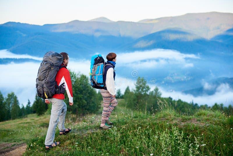 Två turister med ryggsäckar i vandring på berg av Carpathians royaltyfri bild