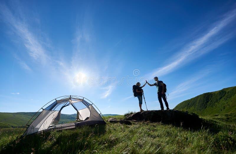 Två turister med trekking pinnar i ryggsäckar ger sig höga fem nära att campa i berg royaltyfri fotografi