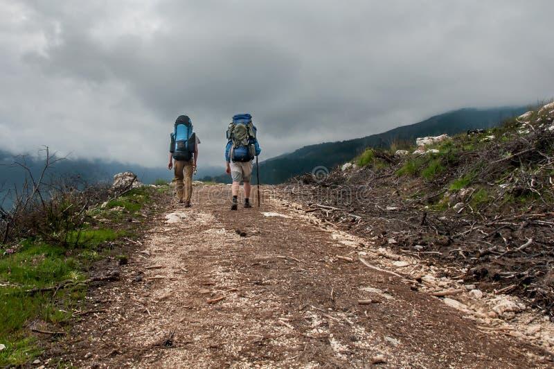 Två turister som fotvandrar längs i bergvägen, Turkiet royaltyfri fotografi