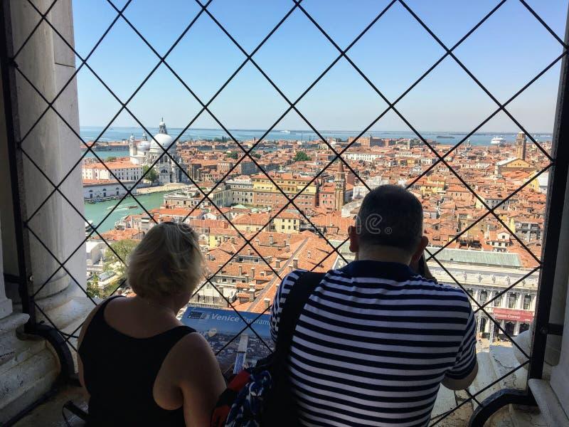 Två turister som uppifrån beundrar sikten av St-fläckcampanilen i St-fläckfyrkant av den oerhörda Venedig, Italien arkivfoton