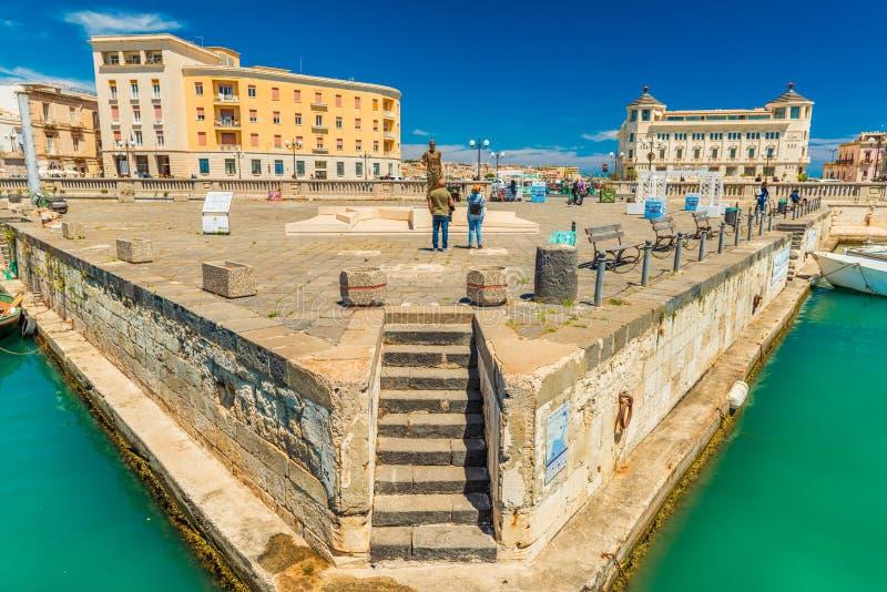 Tv? turister st?r framme av Archimedes Statue n?ra den Umbertino bron, som f?rbinder Syracuse och Ortygia fotografering för bildbyråer