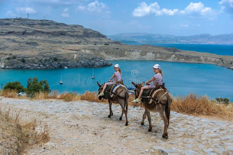 Två tvilling- flickor som rider åsnor på en bergväg till havet rhodes Grekland arkivfoto
