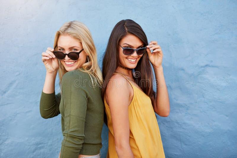 Två ung flickavänner i solglasögon som har gyckel royaltyfria foton