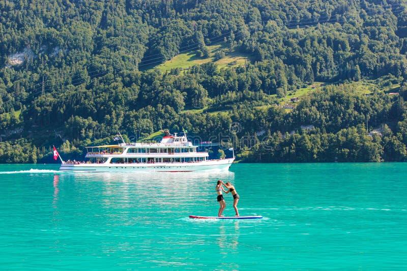 Två ung flickavänner som står på paddleboard på turkossjön Brienz i Schweiz Turist- fartyg i bakgrund switzerland arkivfoton