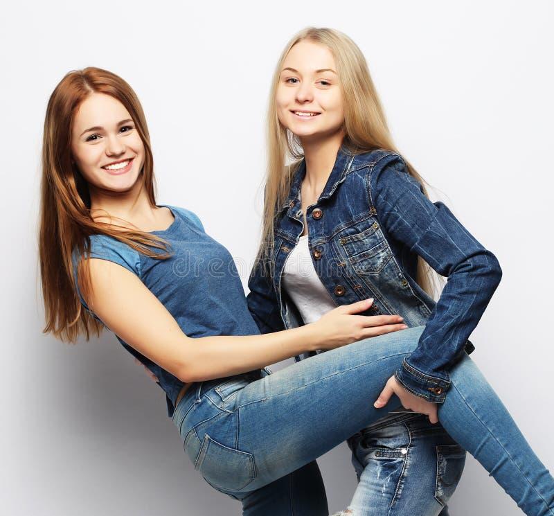 Två ung flickavänner som tillsammans står och har gyckel arkivbilder