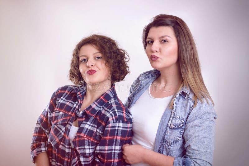Två ung flickavänner som tillsammans står och har gyckel uppvisning royaltyfria bilder