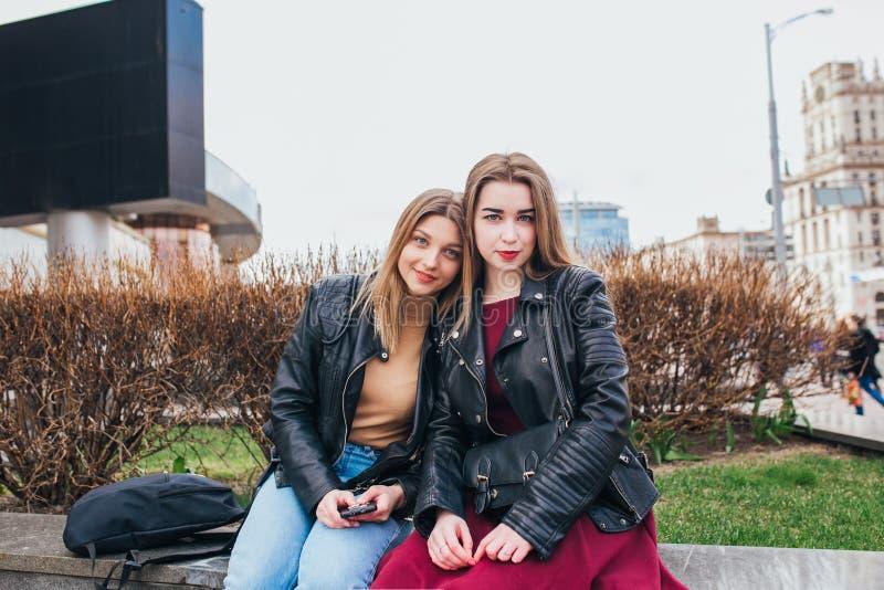Två ung flickavänner som tillsammans utomhus sitter och har roligt livsstil arkivbilder
