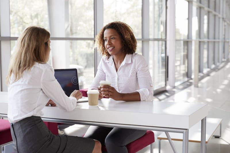 Två unga affärskvinnor på ett möte som talar, nära övre royaltyfri bild