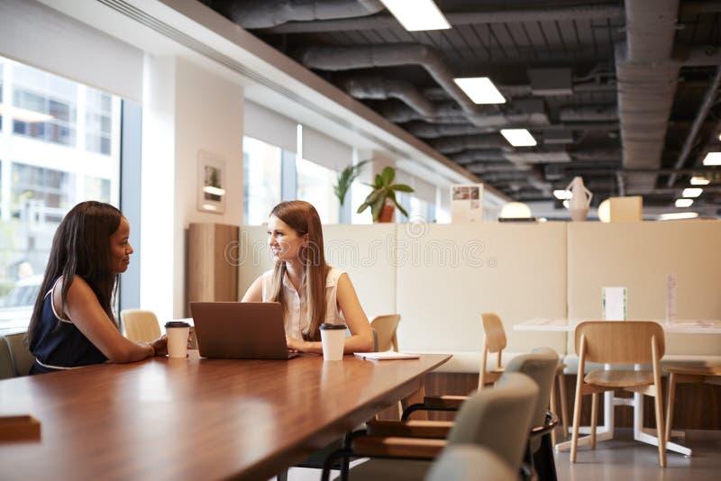Två unga affärskvinnor som har informell intervju i kafeteriaområde på den doktorand- rekryteringbedömningdagen arkivbilder