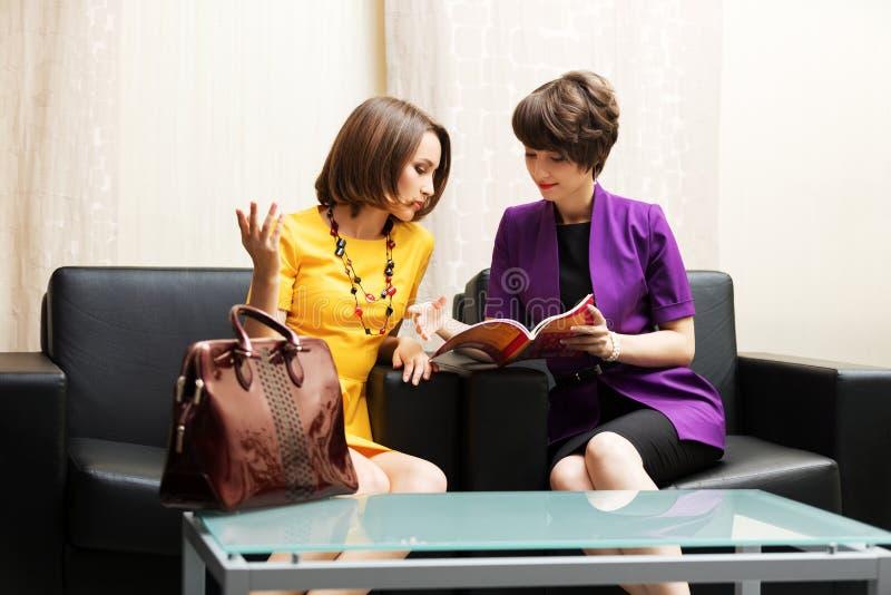 Två unga affärskvinnor som sitter på en soffa arkivbild