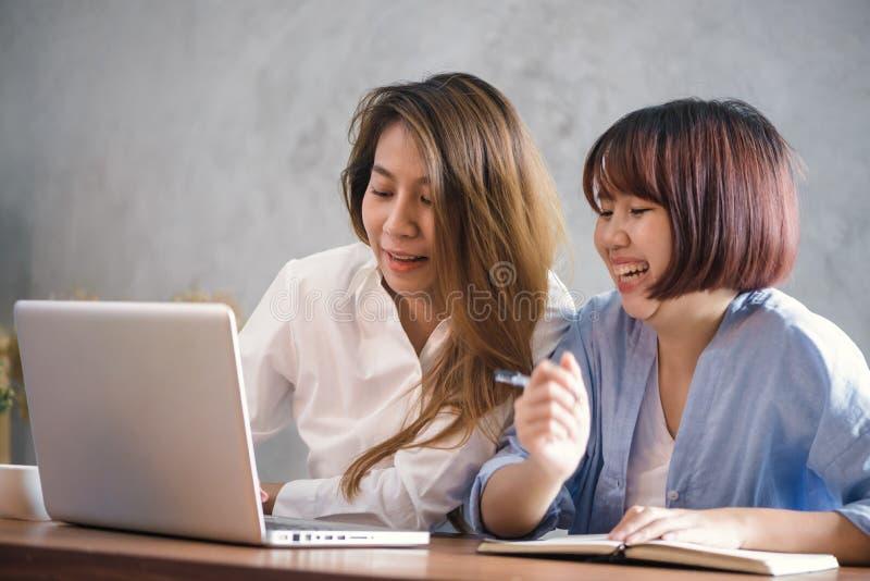 Två unga affärskvinnor som sitter på tabellen i kafé Asiatiska kvinnor som använder bärbara datorn och koppen kaffe Freelancer so arkivbilder