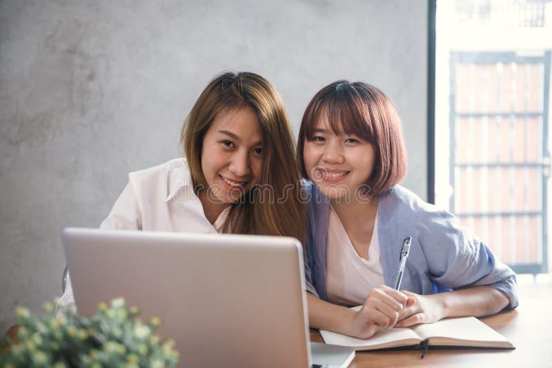 Två unga affärskvinnor som sitter på tabellen i kafé Asiatiska kvinnor som använder bärbara datorn och koppen kaffe Freelancer so royaltyfri bild
