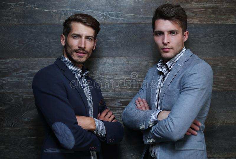 Två unga affärsmän på grå färger arkivfoto