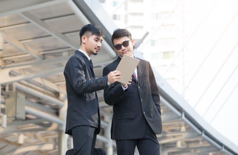 Två unga affärsmän som använder en digital minnestavla till att diskutera proje arkivfoton