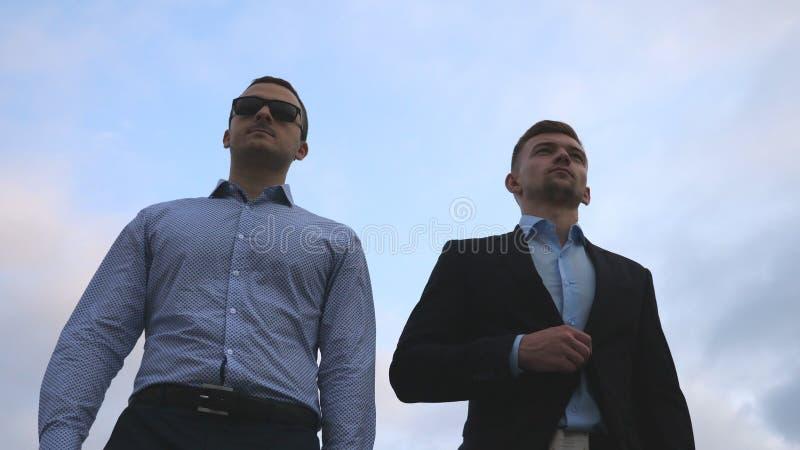 Två unga affärsmän som går i stad med blå himmel på bakgrund Affärsmän som pendlar för att arbeta tillsammans säkert fotografering för bildbyråer