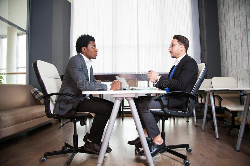 Två unga affärsmän, vitt skrivbord, jobbintervju, teamwork royaltyfri foto