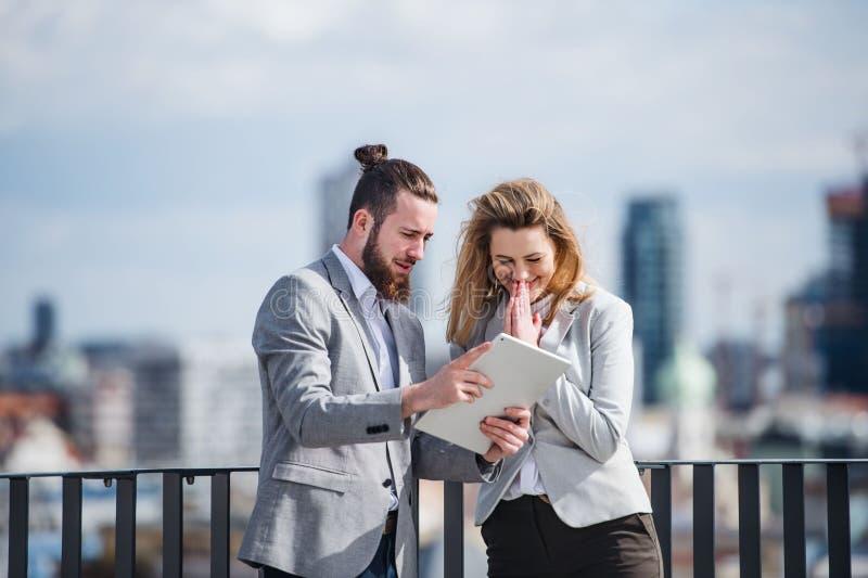 Två unga affärspersoner med minnestavlaanseende på en terrass utanför kontoret som arbetar arkivbild