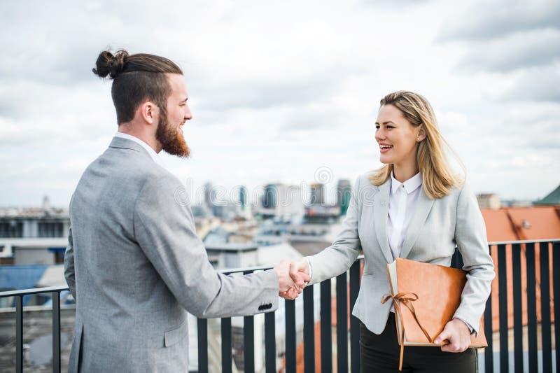 Två unga affärspersoner som står på en terrass utanför kontoret som skakar händer royaltyfri bild