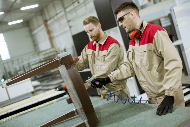 Tv? unga arbetare som monterar m?blemang i fabriken royaltyfri foto