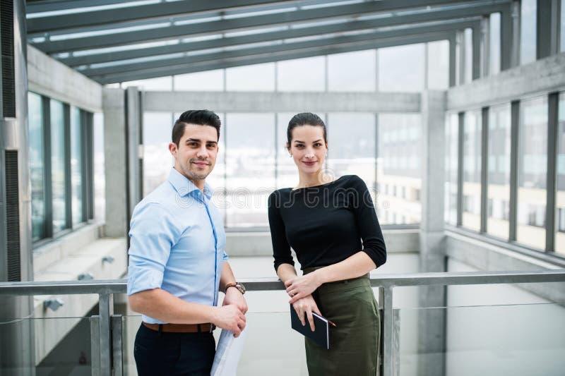 Två unga arkitekter med ritningar som i regeringsställning står och att se kameran royaltyfri fotografi